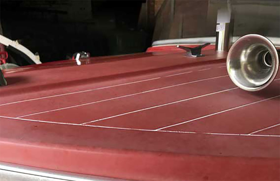 boat with red decking before treatment